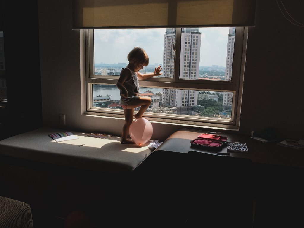 Daughter playing at apartment window